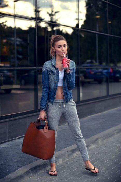 mujer pantalon gris con top, sandalias y chamarra de mezclilla