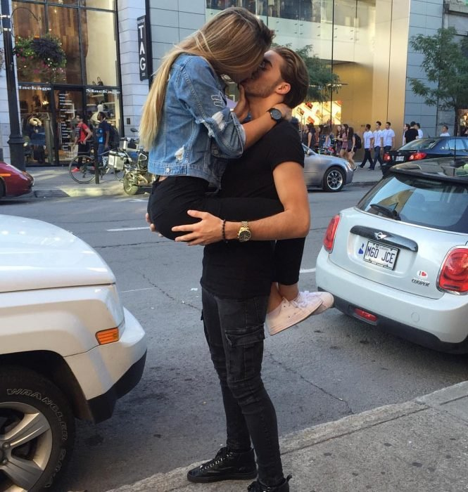 hombre cargando a mujer y abrazándola