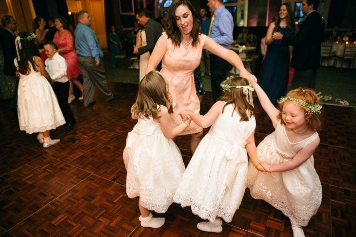 mujer con vestido bailando con niñas