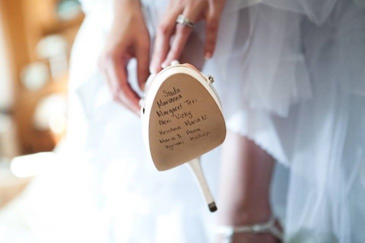 Zapato de una novia en el que se alcanzan a leer los nombres de las solteras.