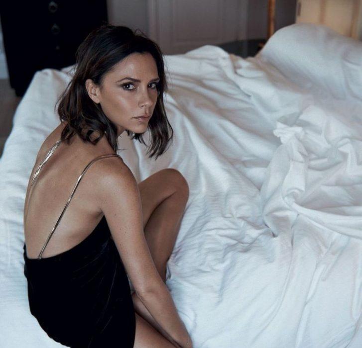 mujer morena de cabello corto con vestido negro sobre cama destendida