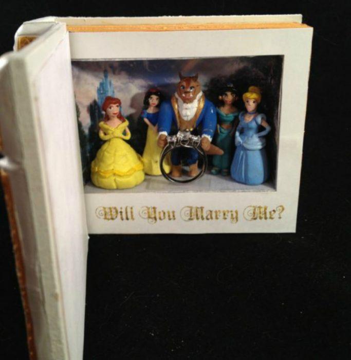 libro con personajes de princesas disney y anillo de compromiso
