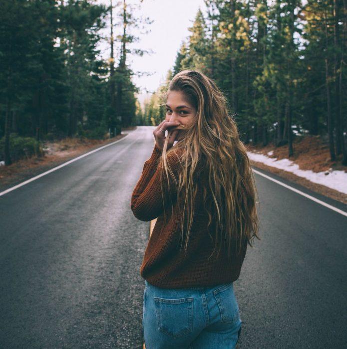 mujer rubia caminando en carretera