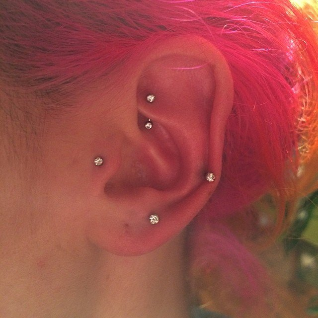 Oreja con constelación formada con piercings.