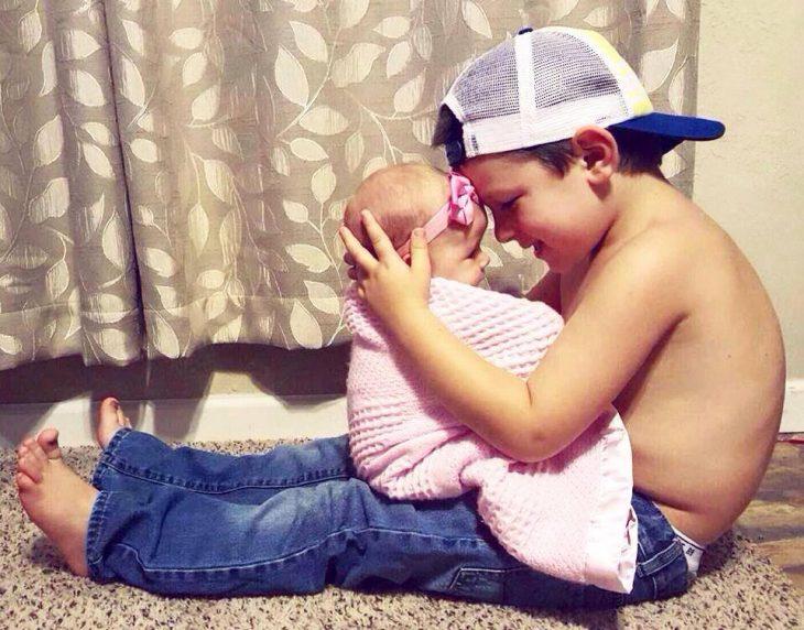 Niño con gorra abrazando a niña bebe