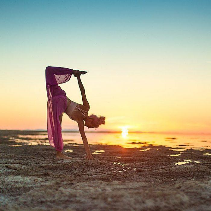mujer se contorsiona en playa con atardecer