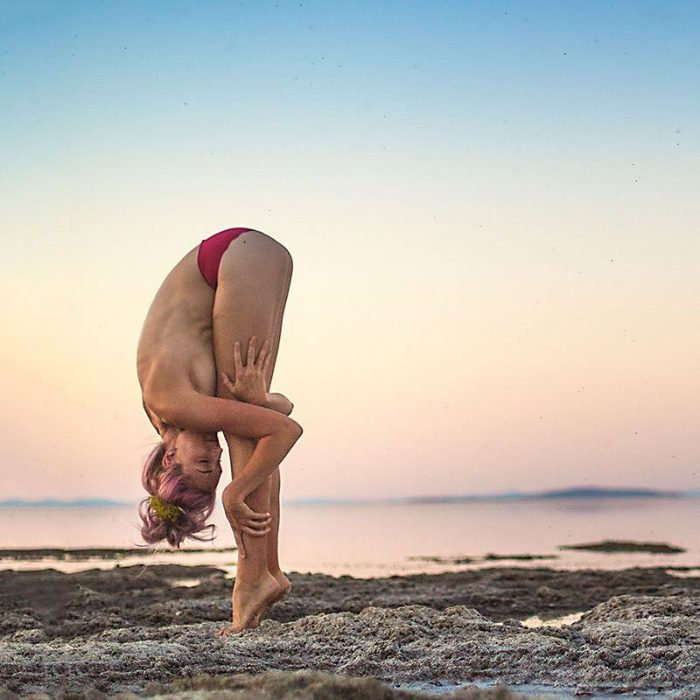 woman on the beach doing yoga
