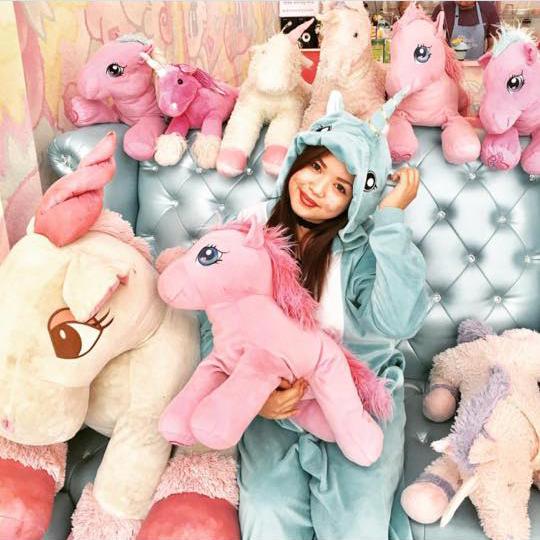 Muchacha rodeada de unicornios.