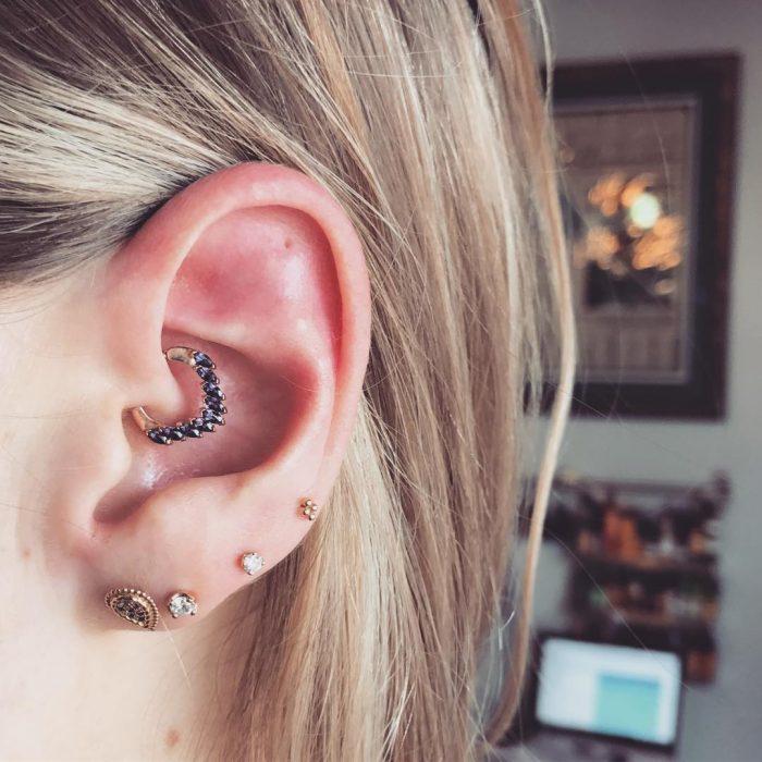 Varios piercings en la oreja.