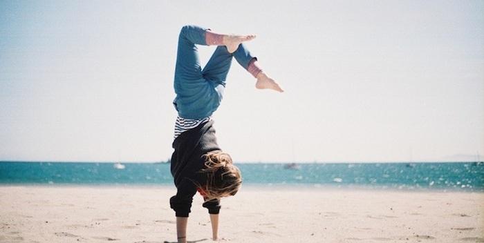 chica caminando de manos en la arena