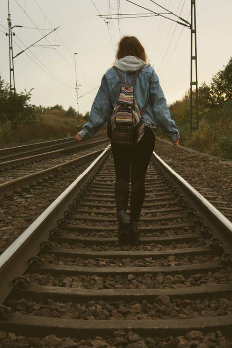 girl walking on train tracks