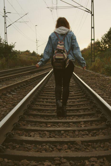 chica caminando por vías del tren