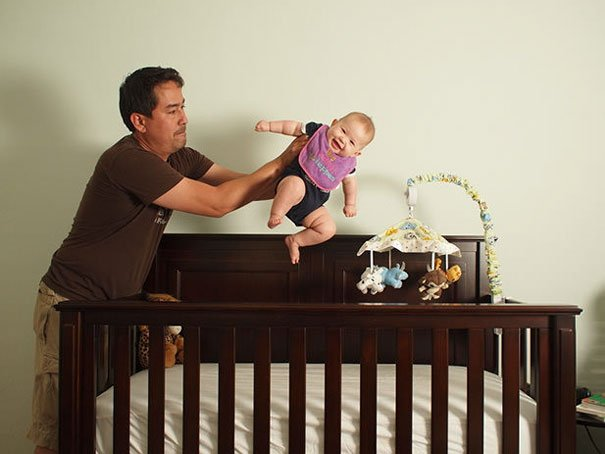 dad holding baby on crib