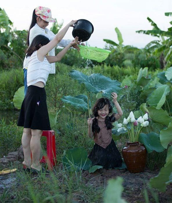 mujeres echan agua encima de hoja para foto