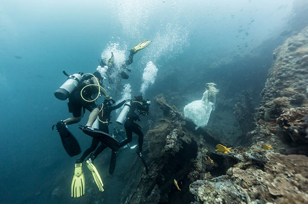 divers helping girl posing in the sea