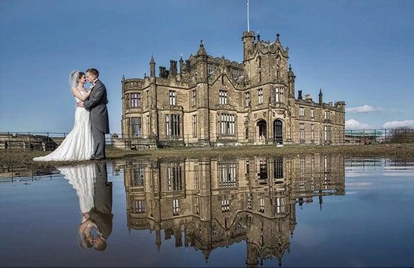 novios besándose frente a castillo