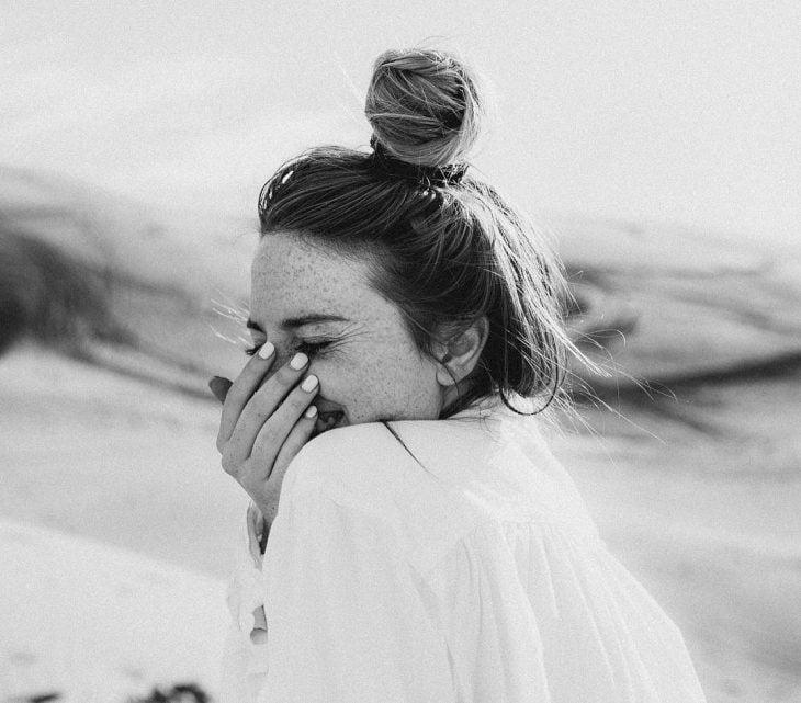 mujer riéndose con mano en la cara