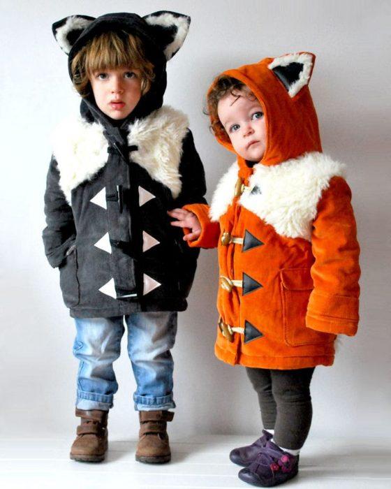 Niños con abrigos de zorrillo y zorro