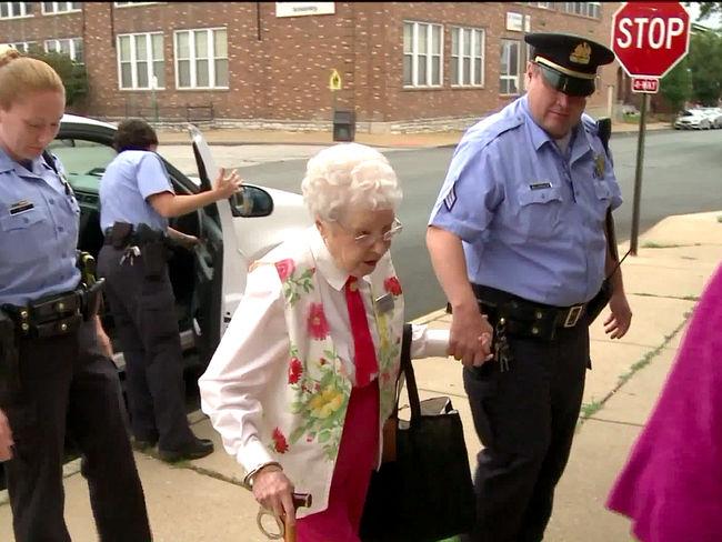 anciana escoltada por policías