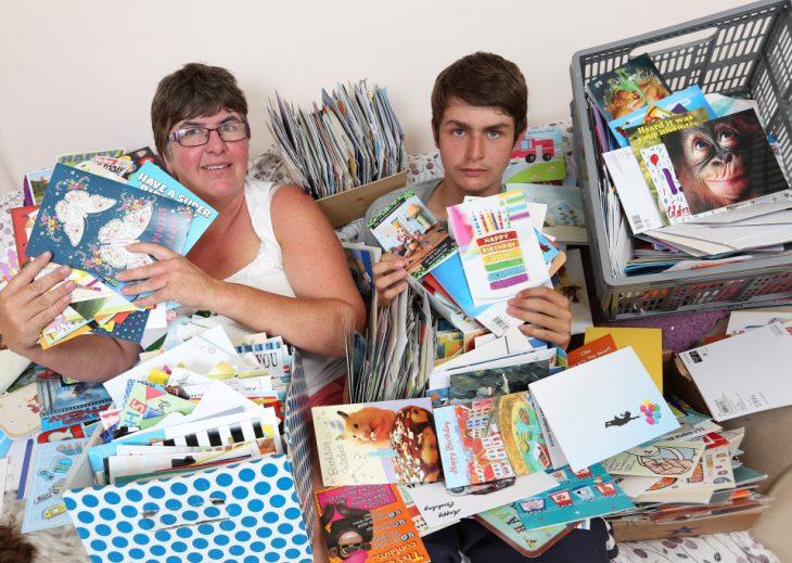 Chico junto con su madre rodeado de cartas de felicitación