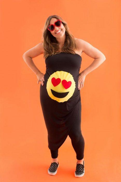 mujer embarazada vestida de negro con emoji