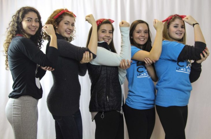 5 mujeres haciendo el símbolo de feminismo