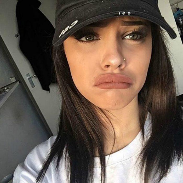 mujer con gorra pone cara triste