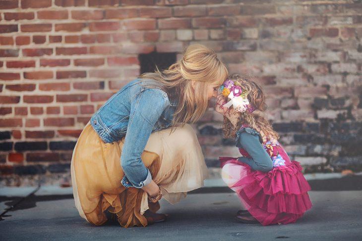 mujer rubia hincada niña con flores en la cabeza