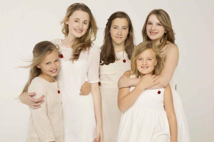 cinco niñas rubias con vestidos blancos