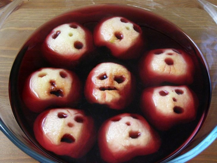 Skull-shaped apples in red wine
