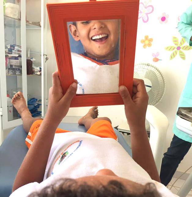 niño sonriendo mientras se mira al espejo