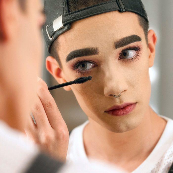 hombre con gorra maquillandose frente al espejo