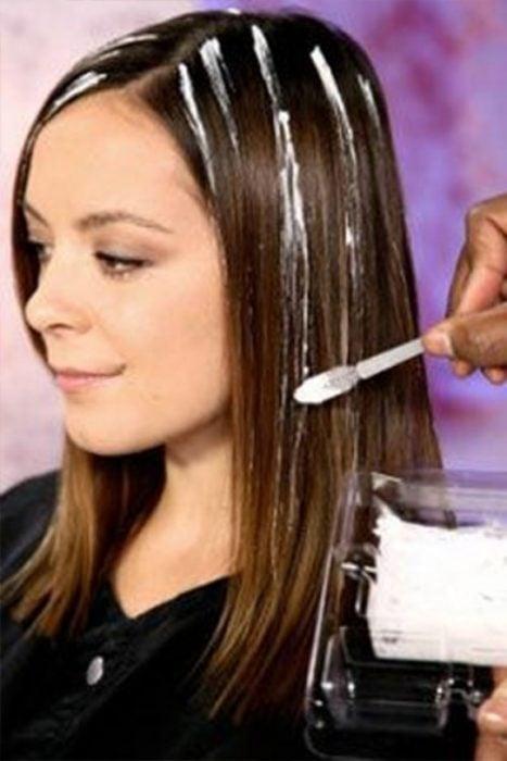 Apllicando tinte al cabello con el cepillo.