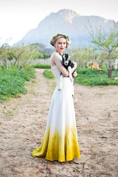 novia rubia cargando cabra con vestido blanco deslavado