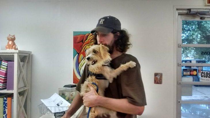hombre de cabello largo con gorra cargando a perro