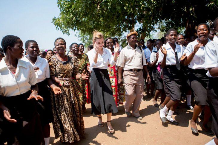 mujer de falda larga junto a personas aplaudiendo