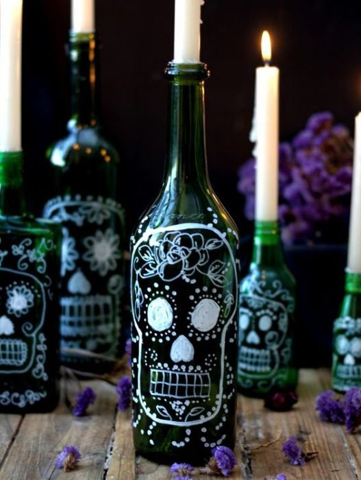 Candles in wine bottles decorated with skulls.