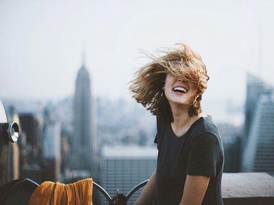 Muchacha sonriendo mientras el cabello le cubre la cara.