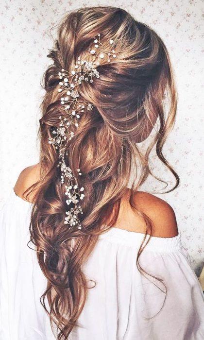 Peinado en cabello largo con accesorios.