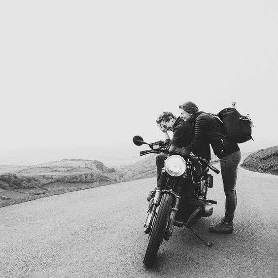 Pareja tomando un break de un paseo en motocicleta.