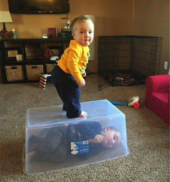 Niño arriba de su hermano metido en un bote.