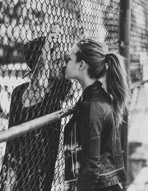 Couple giving a kiss through a fence.
