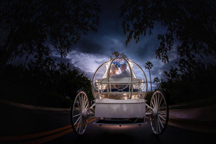 Novios en una carroza de Disney.