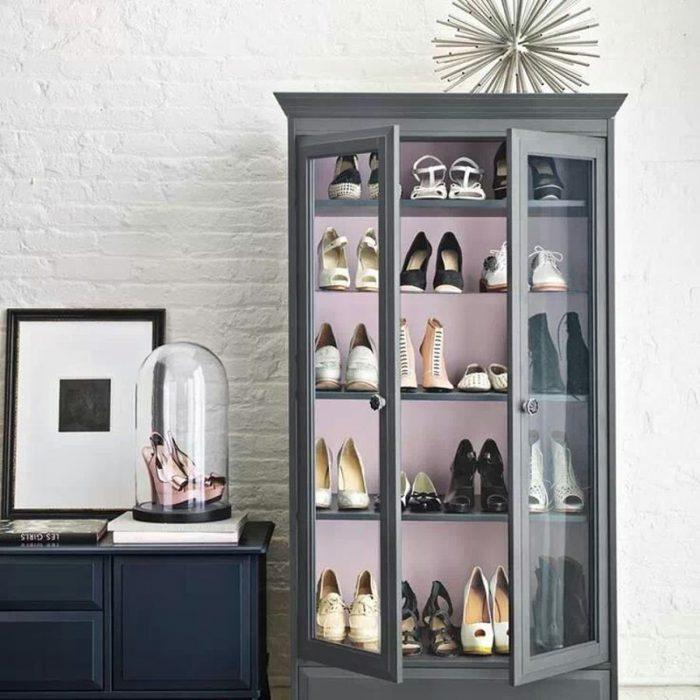 Zapatos organizados en librero antiguo.