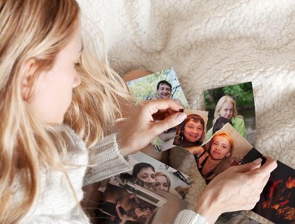 Chica mirando una foto partida en dos.