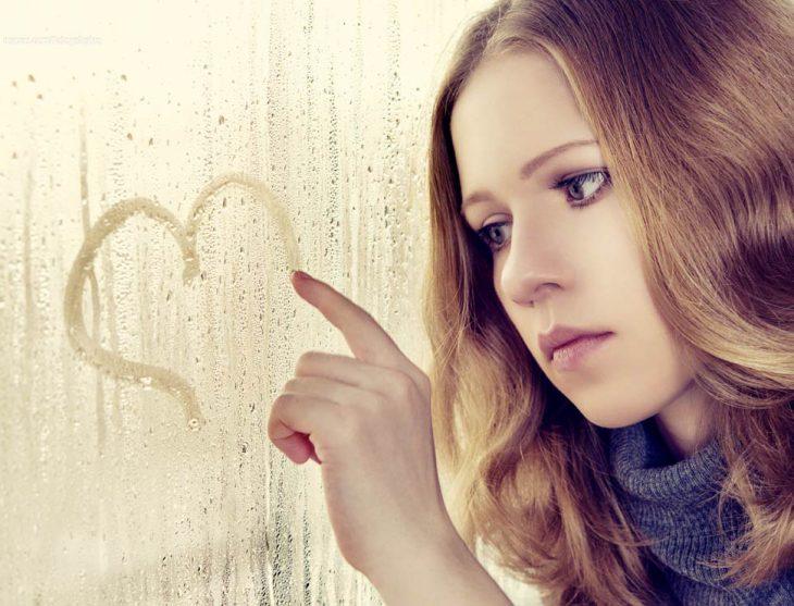 Chica mirando por un vidrio mientras dibuja un corazón.