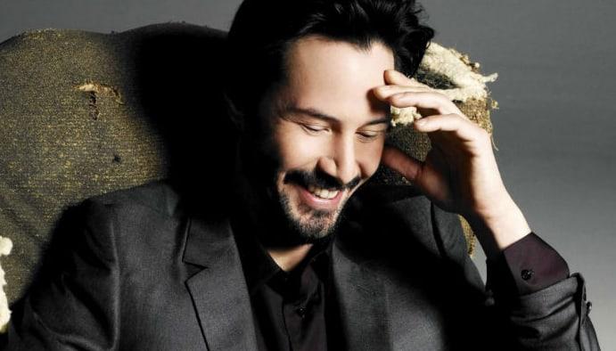 Reeves sonriendo mientras se toma la cabeza.