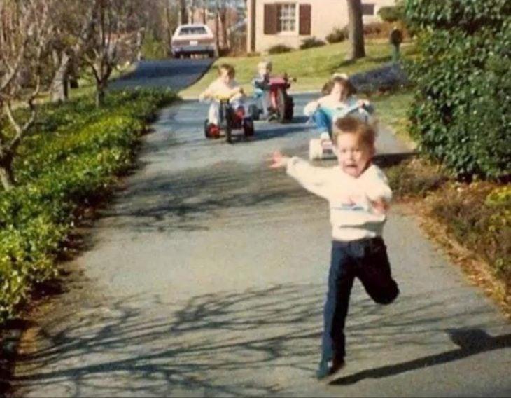 Foto de tres niños corriendo tras su hermano.