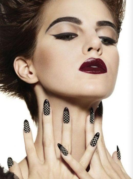 Uñas negras con diseño de cuadros.