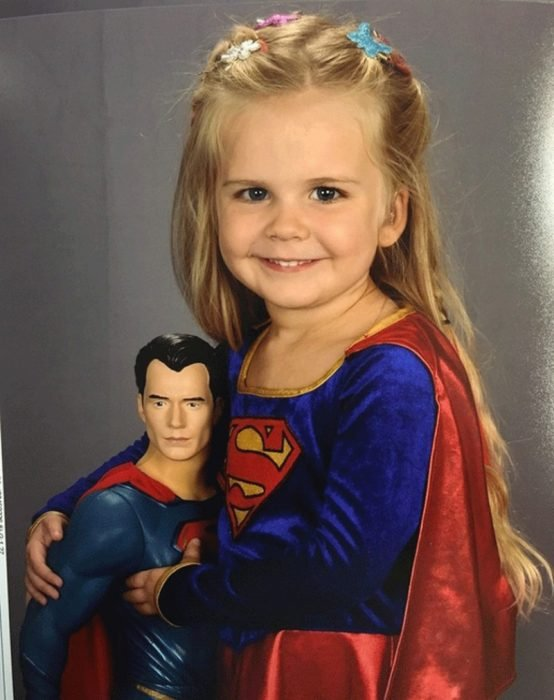 niña rubia con disfraz y juguete de superman